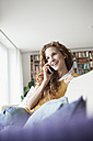 Smiling woman at home sitting on couch talking on cell phone - RBF003129