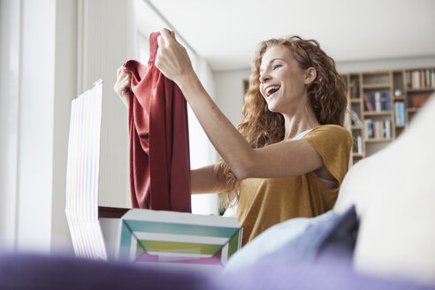 Happy woman at home sitting on couch unpacking parcel with garment - RBF003085