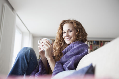 Smiling woman at home sitting on couch holding cup - RBF003090