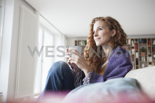 Woman at home sitting on couch holding cup - RBF003091