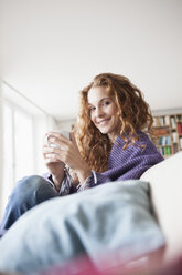 Smiling woman at home sitting on couch holding cup - RBF003092