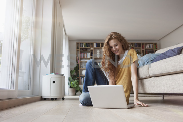 Woman at home sitting on floor using laptop - RBF003103