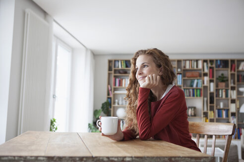 Smiling woman at home sitting at wooden table with cup - RBF003118