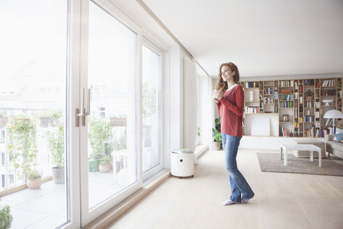 Woman at home looking out of window - RBF003121