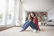 Smiling woman at home sitting on floor - RBF003122