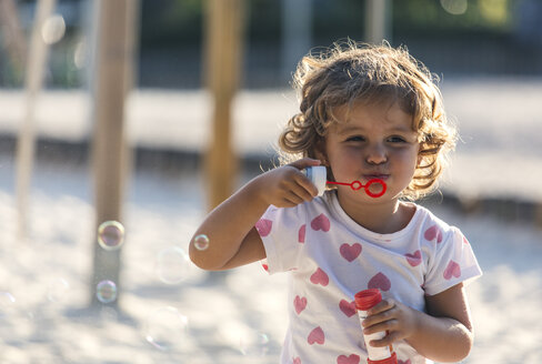 Little girl making soap bubbles at playground - MGOF000478