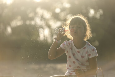 Little girl making soap bubbles in the park at twilight - MGOF000482