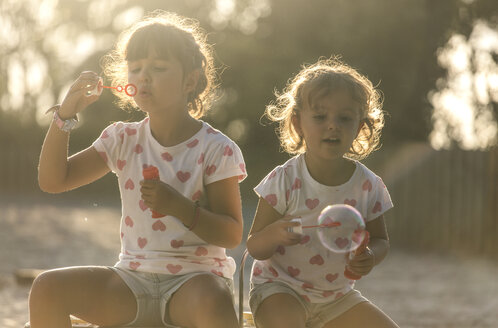 Two little sisters making soap bubbles in the park at twilight - MGOF000484