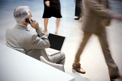 Businessman using cell phone and laptop with people passing by - TOYF001237