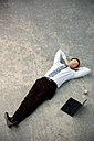 Businessman lying on floor next to laptop - TOYF001243