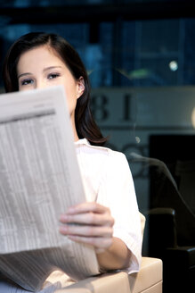 Young businesswoman sitting in armchair reading newspaper - TOYF001255