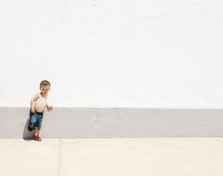Shirtless little boy leaning against a wall - JRFF000001