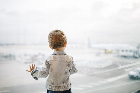 Spain, Barcelona, back view of little boy looking through window at the airport - JRFF000002