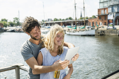 Germany, Luebeck, happy couple at the harbor with digital tablet - FMKF001848