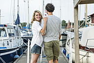 Germany, Luebeck, smiling couple at marina - FMKF001858