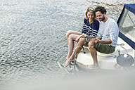 Couple on boat using digital tablet - FMKF001894