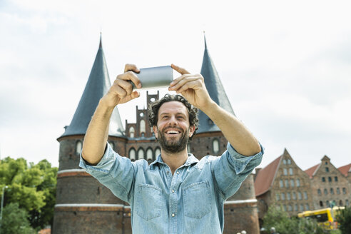 Germany, Luebeck, man taking selfie in front of the Holsten Gate - FMKF001882