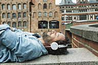 Germany, Luebeck, man with headphones relaxing in the city - FMKF001891