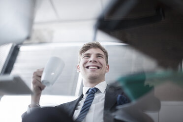Smiling businessman holding coffee mug in office - ZEF007137