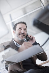 Smiling businessman talking on phone in office - ZEF007139