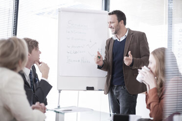 Businessman at flip chart talking to colleagues - ZEF007150