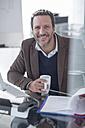 Portrait of smiling businessman at desk - ZEF007154