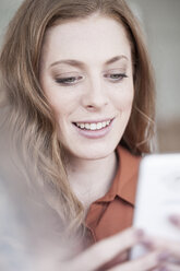 Smiling young woman looking at cell phone - ZEF007164