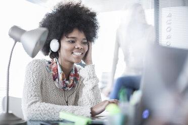 Smiling woman in office working on laptop wearing headphones - ZEF007461