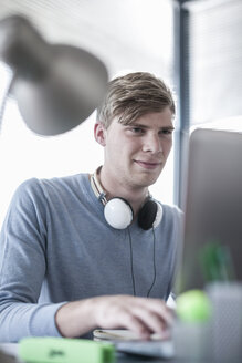 Man at office desk wearing headphones working on laptop - ZEF007175