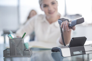 Woman in office holding telephone receiver - ZEF007193