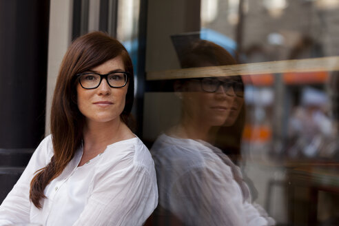 Portrait of woman with brown hair wearing glasses leaning against windowpane of a cafe - HCF000143