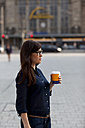 Germany, Leipzig, woman with coffee to go standing on a a square - HCF000146