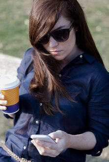 Portrait of woman wearing sunglasses sitting on a park bench with smartphone and coffe to go - HCF000147