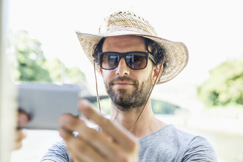 Man wearing straw hat and sunglasses taking a selfie - FMKF001916