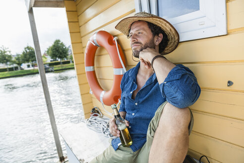 Relaxed man on a house boat with beer bottle - FMKF001939