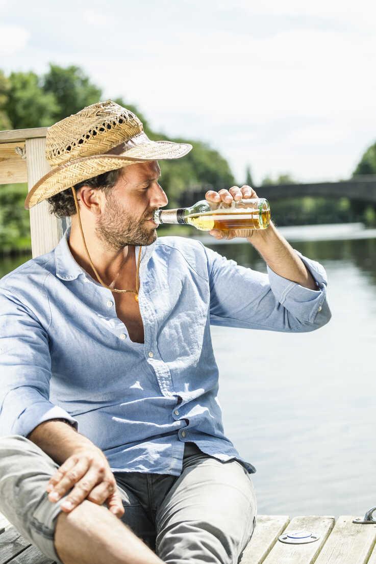 Man sitting on platform at the waterside drinking beer - FMKF001968 - Jo Kirchherr/Westend61