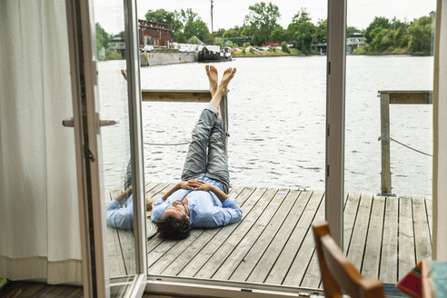 Man lying on wooden deck of a house boat - FMKF001973