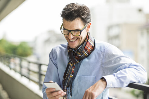 Smiling businessman looking at his smartphone - UUF005365