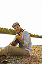 Portrait of happy man playing guitar at riverside in the evening - UUF005385