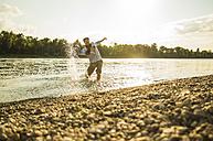 Man standing at riverside splashing with water - UUF005390