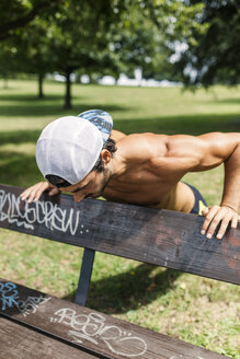 Athletic young man doing workout in the park - MGOF000486