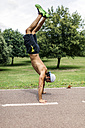 Athletic young man doing handstand in the park - MGOF000494