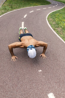 Athletic young man doing pushups in the park - MGOF000496