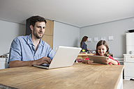 Man and his little daughter sitting at kitchen table using laptop and digital tablet - RBF003372