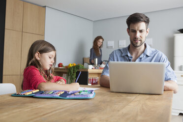 Man sitting at kitchen table using laptop while his little daughter painting - RBF003373