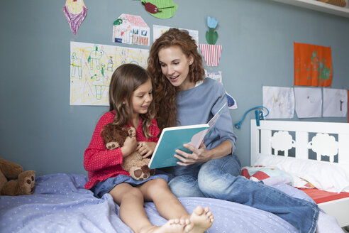 Mother and little daughter sitting together on bed in children's room reading a book - RBF003374
