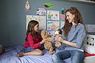 Mother and little daughter sitting on bed in children's room playing together with soft toys - RBF003376