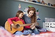 Little girl playing guitar while her mother listening - RBF003385