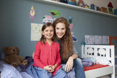 Portrait of mother and little daughter sitting side by side on bed in children's room - RBF003387