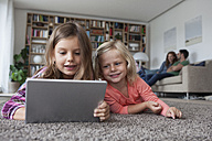 Portrait of two little sisters lying on the floor at living room with digital tablet - RBF003396